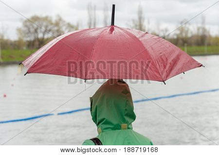 Someone wearing a green raincoat and holding a red umbrella on a rainy day