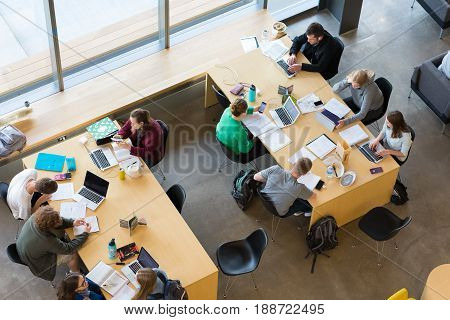 EUGENE, OR - MAY 17, 2017: College students share a table and study together at the Erb Memorial Union building on the University of Oregon campus.