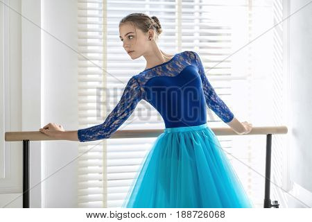 Beautiful ballerina stands next to the ballet barre and holds her hands on it on the window background. She wears a lace blue leotard with a cyan tutu and looks to the side. Indoors.