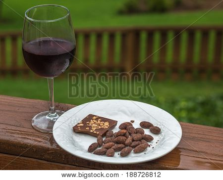 Chocolate covered almonds and chocolate almonds on a white plate with a glass of red wine on a wooden porch after a spring rain