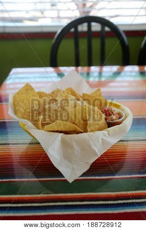 Chips and Salsa. Fresh Deep Fried Corn Chips and Fresh Tomato Salsa in a yellow plastic basket with a paper lining on a stripped colored cloth table cloth.