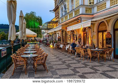 PRAGUE, CZECH REPUBLIC - SEPTEMBER 22, 2015: Outdoor restaurant at evening in Prague - capital and largest city of Bohemia, fifth most visited in Europe with more than 6.4 million visitors annually.