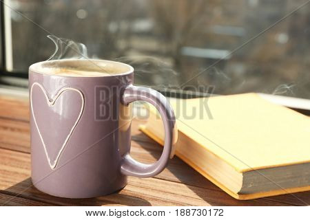 Cup with delicious coffee and book on window sill