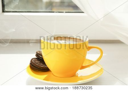 Yellow cup of delicious coffee on window sill