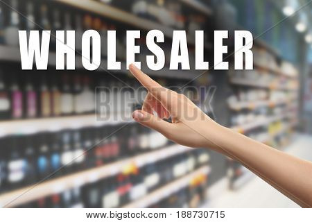 Wholesaler concept. Female hand pointing on text and blurred background of shelves in supermarket