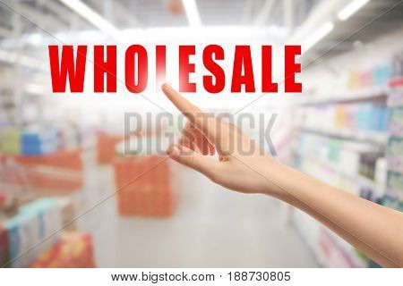 Wholesale concept. Female hand pointing on text and blurred background of shelves in supermarket