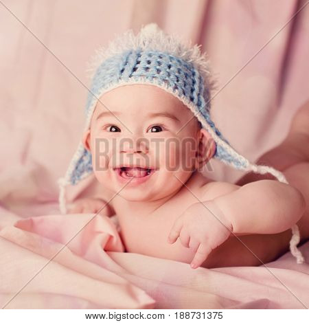 Beautiful expressive adorable big-eared baby laughing and smiling, showing tongue