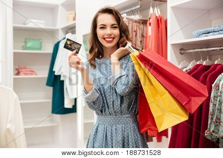 Photo of smiling young woman shopper in blue dress in shop choosing clothes. Looking at camera holding debit card.