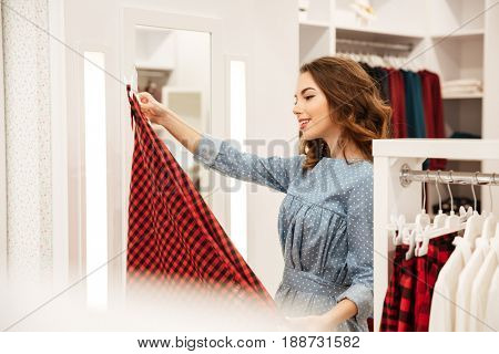 Image of smiling woman shopper in blue dress choosing clothes in shop. Looking aside.