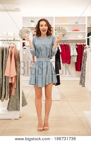 Happy woman holding money wile shopping