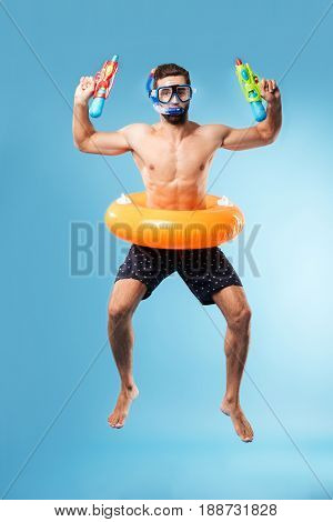 Young funny man jumping wearing swimming circle and glasses and holding water guns isolated over blue