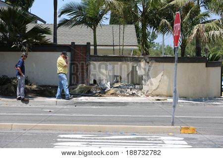 Lake Forest, California, May 23, 2017: City Inspectors assess the damage of a city retaining wall after a single truck accident containing swimming pool chemicals drives into it causing damage.