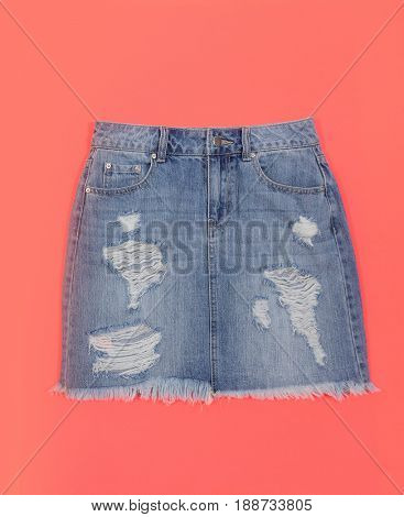 Blue denim skirt isolated on blue and orange background