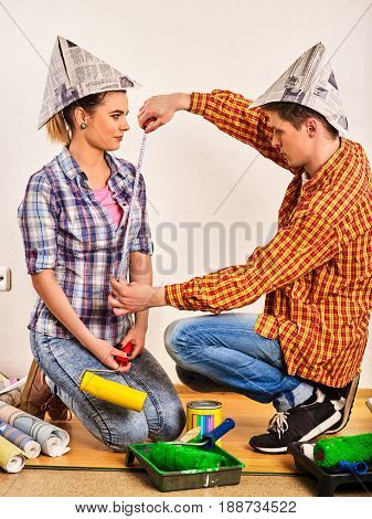 Repair family by happy couple building home using spirit level to measure. Woman and man in newspaper cap renovation apartment.