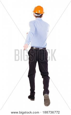 Back view of running engineer in helmet. Walking guy in motion. Rear view people collection. Backside view of person. Isolated over white background. Foreman runs toward the building.