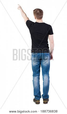 Back view of  pointing young men in  t-shirt and jeans. Young guy  gesture. Rear view people collection.  backside view of person.  . A man in a black jacket and is showing one of his hands up.