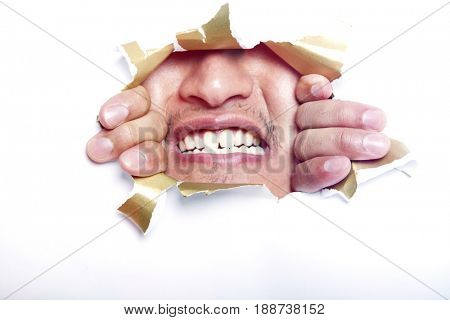 Young Korean man looking through ripped paper hole