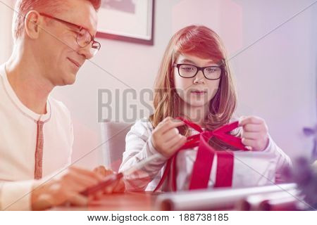Father and daughter wrapping Christmas present at home