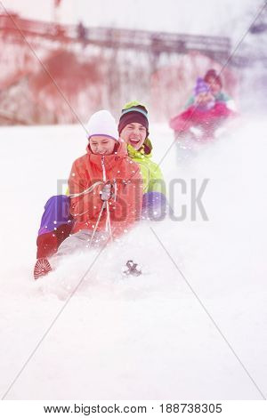 Young couple enjoying sled ride on snow covered slope