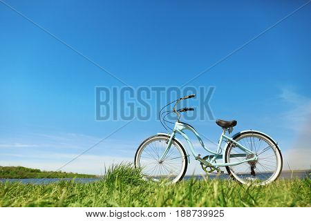 Blue bicycle standing on grass near river
