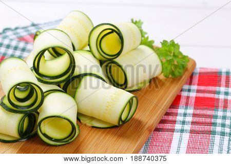raw zucchini strips rolled on wooden cutting board - close up