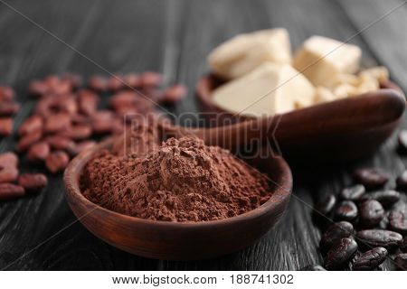 Wooden bowl with cocoa powder on table