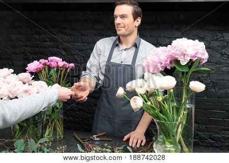 Florist receiving discount card from regular customer in flower shop