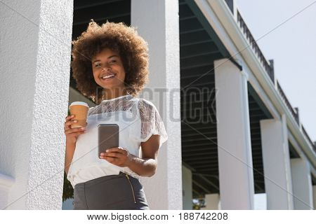 Portrait of young woman using mobile phone while holding disposable cup by building on sunny day