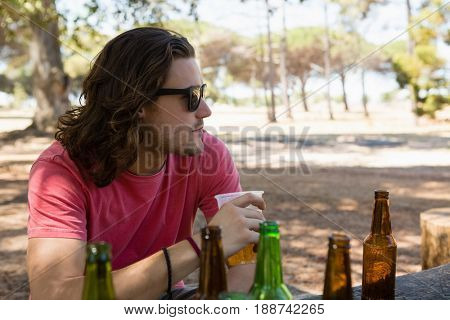 Young man in sunglasses having beer in the park