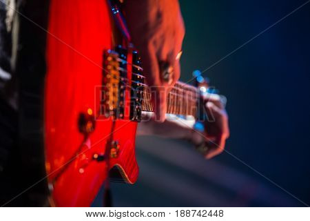 Close-up of guitarist playing guitar on stage in nightclub