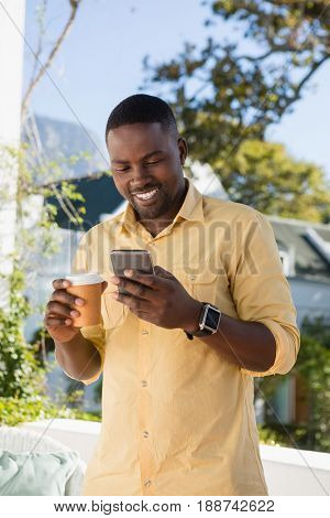 Happy young man using mobile phone while holding disposable coffee cup at cafe