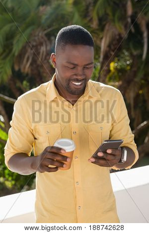 Smiling young man using mobile phone while holding disposable coffee cup at cafe