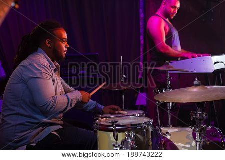 Drummer playing on drum set on stage in nightclub