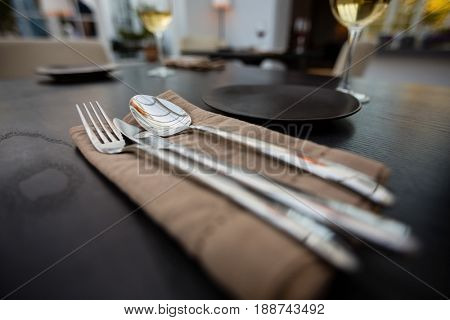 Close up of eating utensils and napkin on table at restaurant