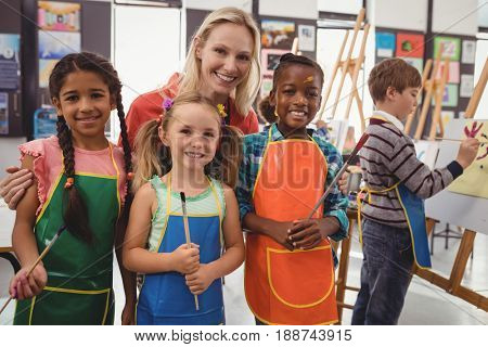 Portrait of teacher and schoolkid standing together in drawing class