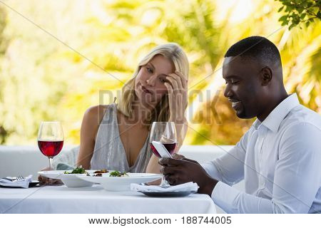 Irritated woman looking at man using phone at table in restaurant