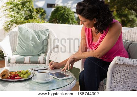 Confident woman using digital tablet while writing on paper in restaurant