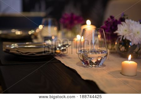 Close up of drinking glass by lit candles on dining table at restaurant