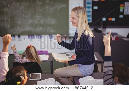 Schoolkids raising their hands while teacher teaching in classroom at school
