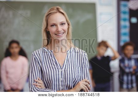 Portrait of happy teacher standing with arms crossed in classroom at school