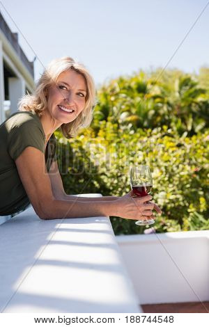 Smiling mid adult woman with red wine leaning on retaining wall in restaurant