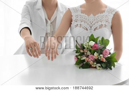 Gay wedding concept. Happy married lesbian couple on light background, closeup