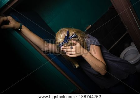 Unconscious drunk woman standing in the washroom