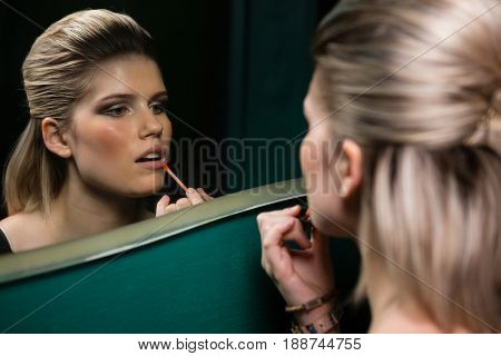 Woman applying lips gloss while looking at mirror in washroom