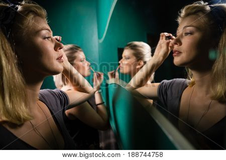 Woman applying eyeliner while looking at mirror in washroom