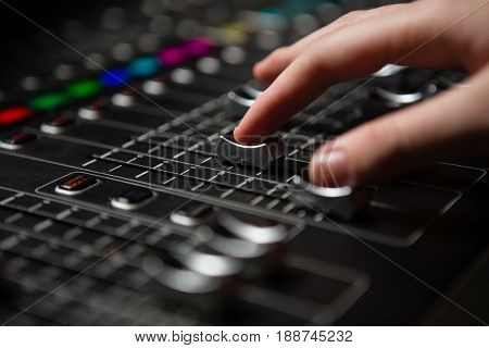 Hand of female audio engineer using sound mixer in recording studio