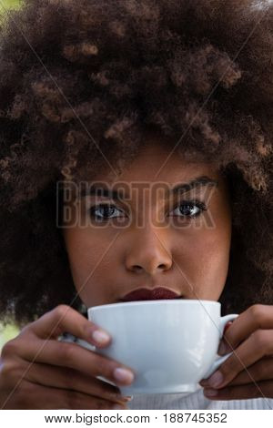 Close up portrait of young woman with frizzy hair holding coffee cup
