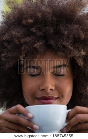 Close up of smiling woman with frizzy hair smelling coffee