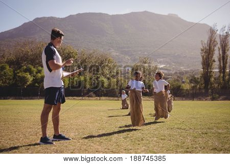 Coach monitoring schoolgirls during sack race in park on a sunny day
