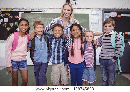 Happy teacher standing with schoolkids in classroom at school